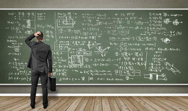 Foto: Mann steht vor Wandtafel mit vielen Formeln